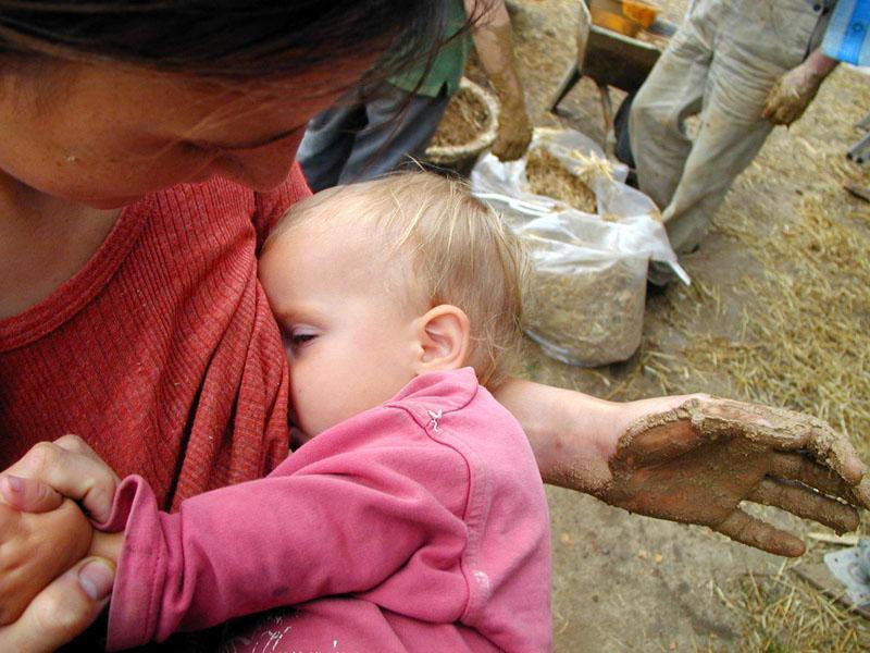И даже кормящие мамы участвуют в строительстве соломенного дома...