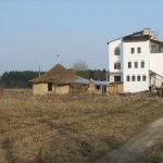 На фоне трехэтажного кирпчиного дом из соломы теряется...