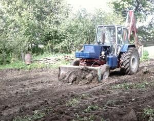Трактор снимает плодородный слой на участке
