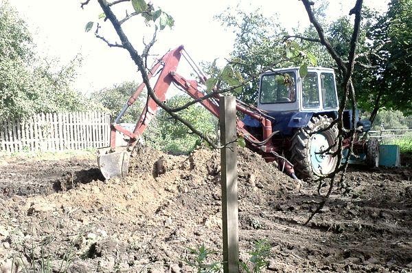 Трактор копает землю
