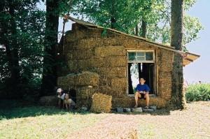 Ребенок сидит на пороге соломенного дома