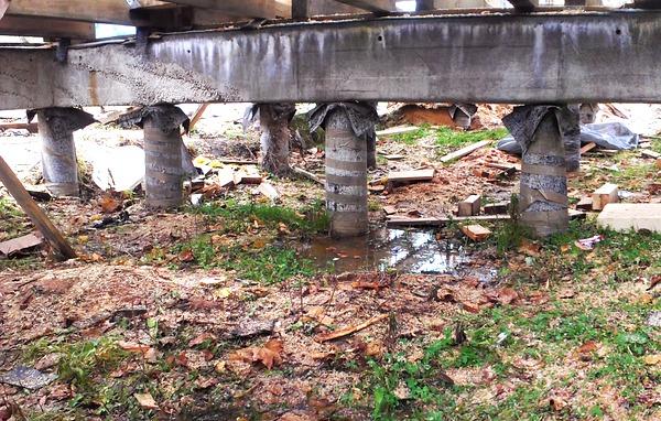 Возле столбиков фундамента стоит вода