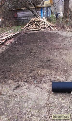 Вскопанная и выравненная грядка под баклажаны. На земле рулон спанбонда