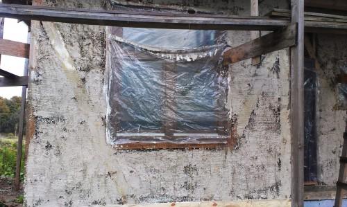 Стена соломенного дома после 1 слоя штукатурки