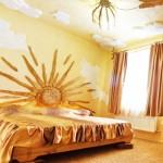 Стена оштукатурена желтым, на ней солнце из дерева