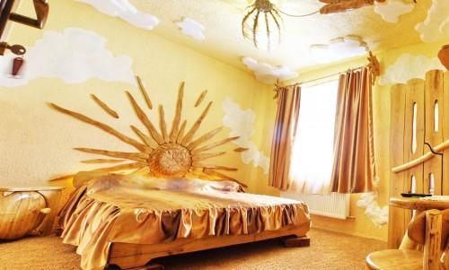 Стена оштукатурена желтым, на ней солнце из дерева. Потолок со стилизованными облаками. Кровать из дерева. Все выглядит так, будто над кроватью встает солнце...