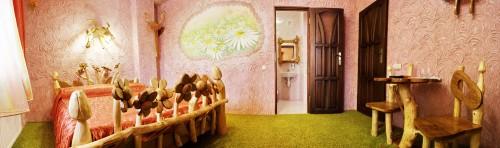 Фактурная штукатурка на стенах, в одном месте сделана стилизация под цветущий луг. Кровать из дерева соответственно сделана с деревнными цветочками. Остальные элементы тоже из деерва