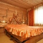 Широкая кровать, украшения из дерева на стенах