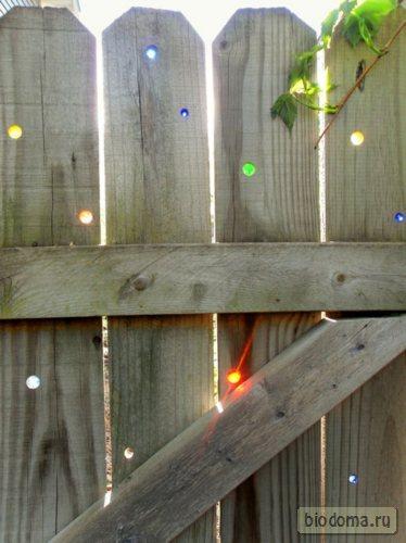 Еще один оригинальный взгляд на калитку - просто просверлить дырочки и вставить в них разноцветные стеклышки. Любая стандартная калитка заиграет всеми цветами радуги - в прямом смысле слова!