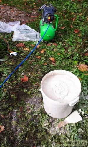 Строительный миксер и разведенная штукатурка лежат на земле