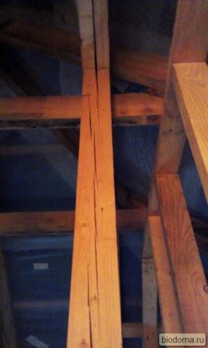 косяк строителей с опорной балкой под крышей в деревянном каркасе
