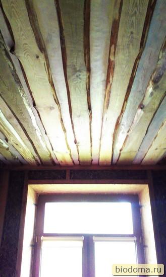 вид на потолок из досок и окно
