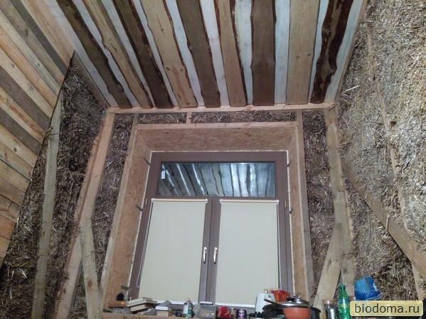 соломенная стена, необрезные доски на потолке, деревянное окно