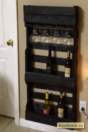 Полочка для вина и бокалов из деревянных паллет окрашены темно-коричневый или черный цвет, что на фоне светлой стены создает такой кантри-стиль...